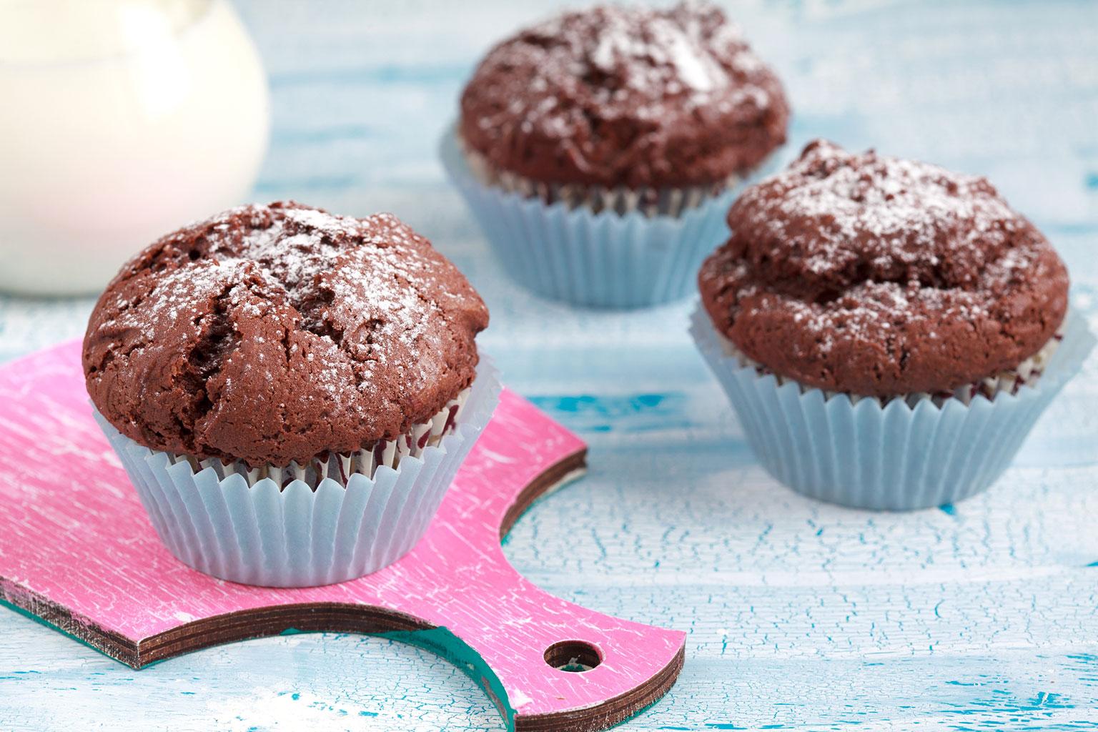 Посыпать шоколадные кексы сахарной пудрой