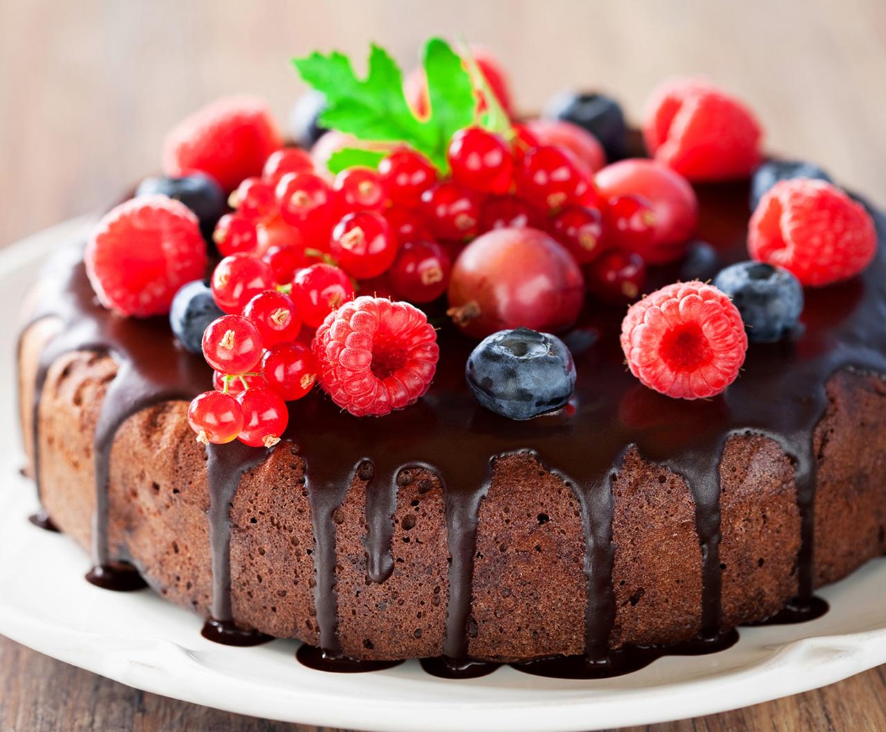 Шоколадный кекс, украшенный ягодами и растопленным шоколадом