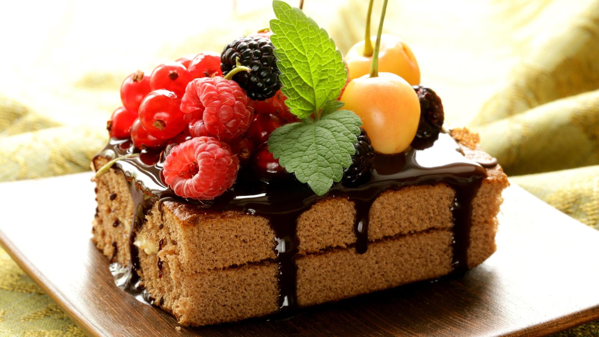 Украсить ягодами шоколадное бисквитное пирожное