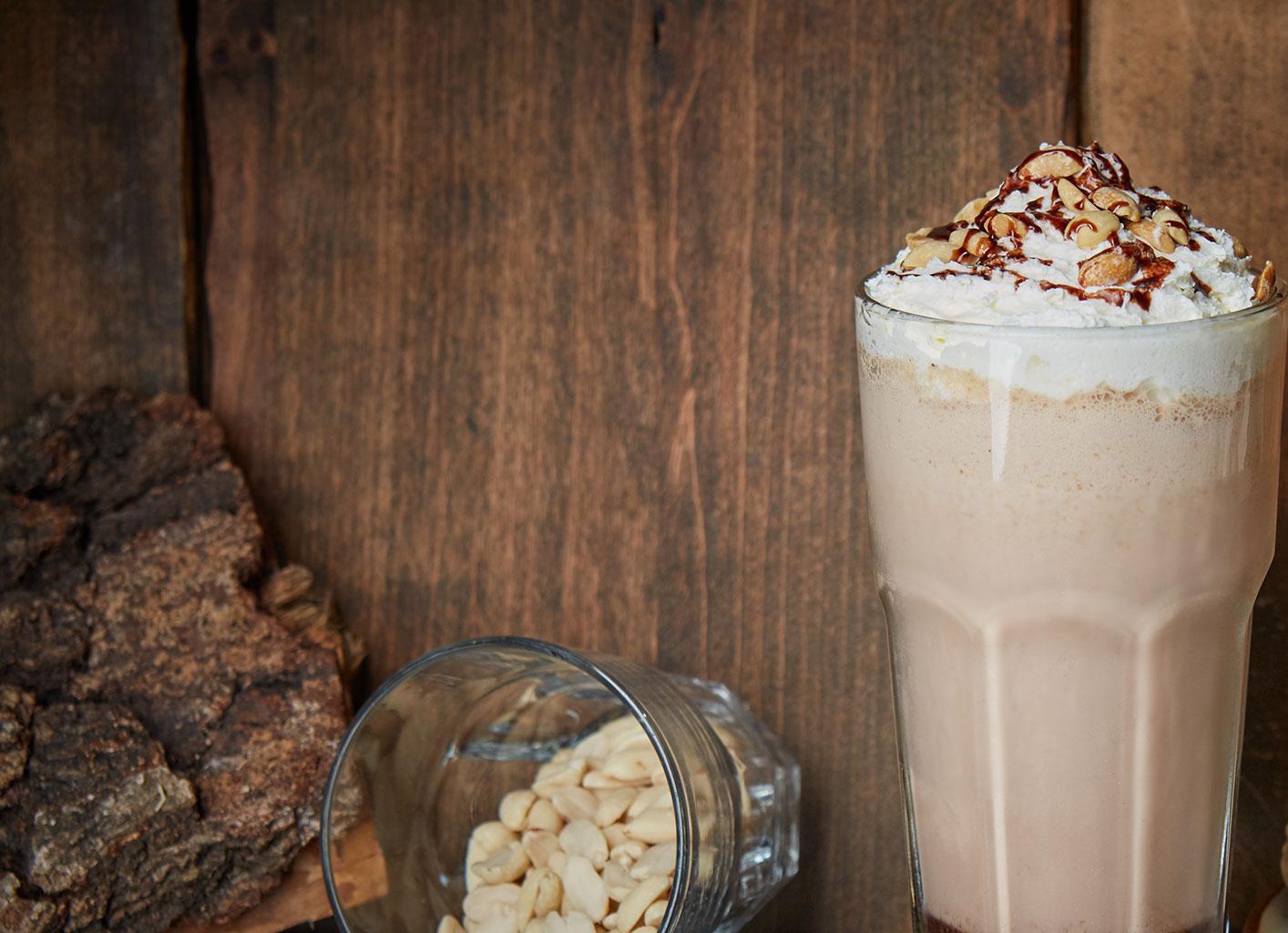 Шоколадный коктель, украшенный сливками и орехами
