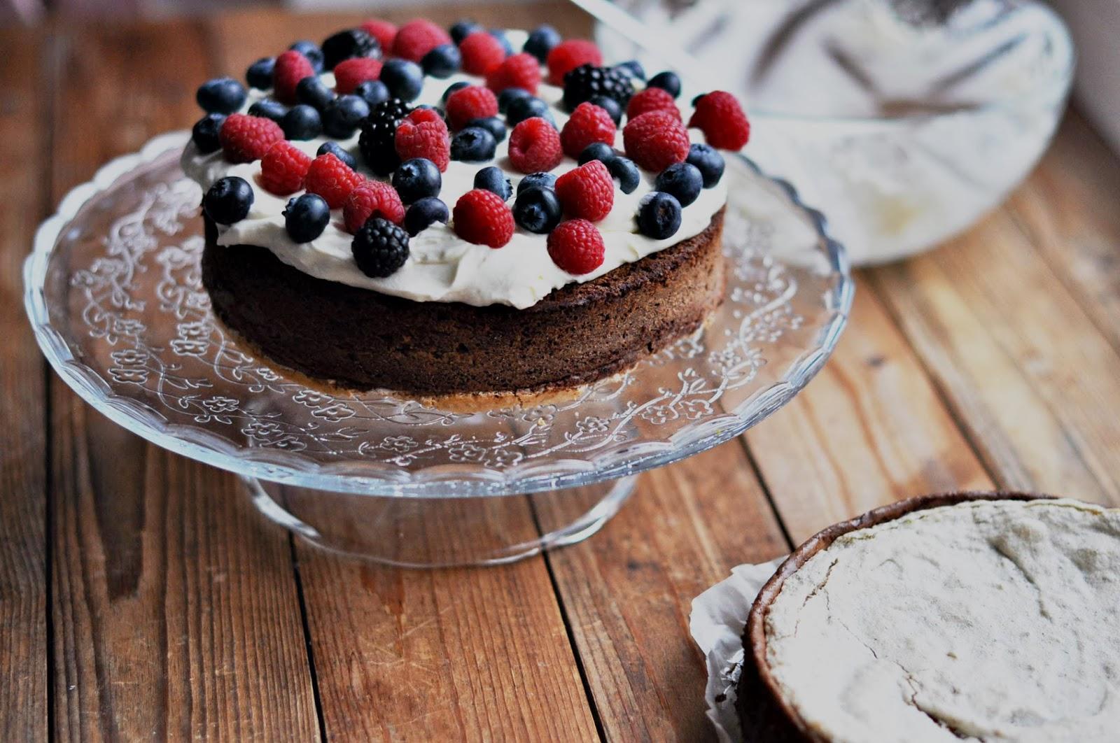 Шоколадный бисквит, украшенный ягодами и кремом